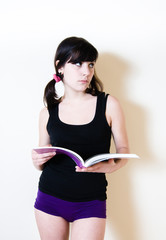 Young pretty brunette in short standing and reading a book while