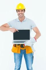 Happy carpenter holding laptop