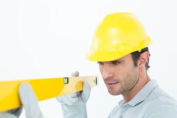 Carpenter wearing hard hat while using spirit level