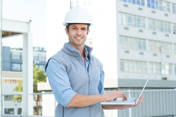 Confident male architect using laptop