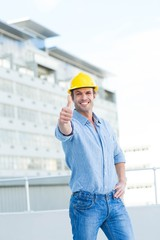 Smiling male architect gesturing thumbs up