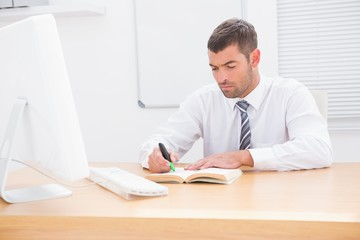 Businessman sitting at desk reading a book