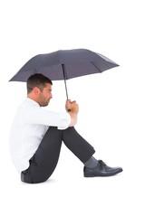 Businessman sitting on the floor with black umbrella