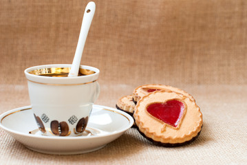 cup of coffee and a cookie with a heart of marmalade