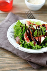 Salad with figs, lettuce and balsamic sauce in a white bowl