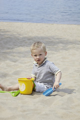 A young boy playing in the sand.