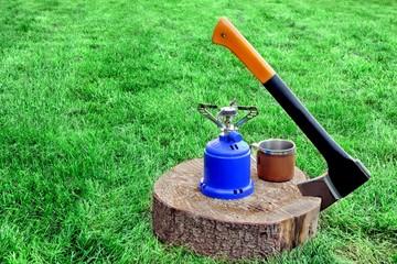 Lumberjack Axe, Gas Burner, Tea Mug on Tree Cross Section