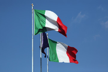 National flags of Italy and a flag of the European Union.