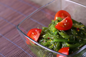 Seaweed salad with slices of cherry tomato in glass bowl