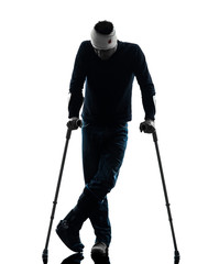 injured man standing with crutches silhouette