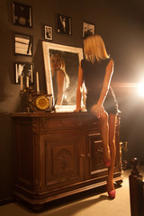 adorable girl sitting on the nightstand next to the mirror in a