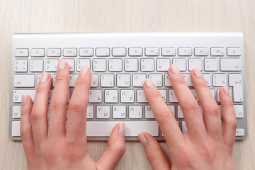 Female hands with keyboard on wooden desktop background