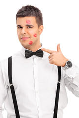 Vertical shot of a man covered in lipstick kiss marks