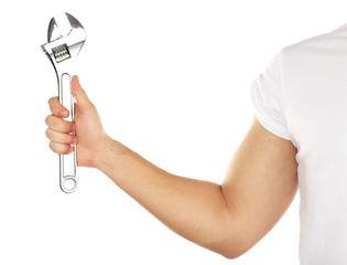 Adjustable wrench in male hand isolated on white