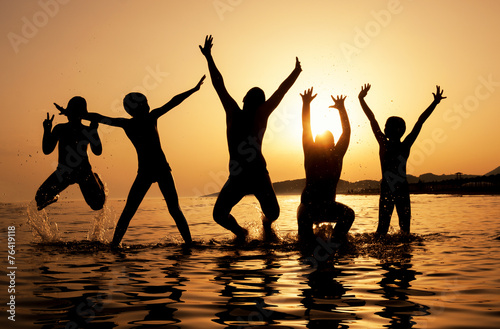 Silhouette of kids jumping on the beach