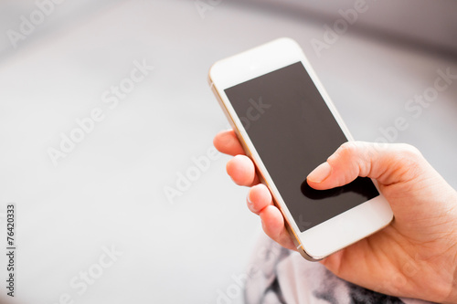 Woman holding smartphone - 76420333