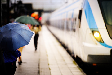 Travellers with umbrellas waiting for train