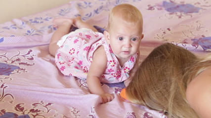 child in pink dress lay on the bed and play with mother hair