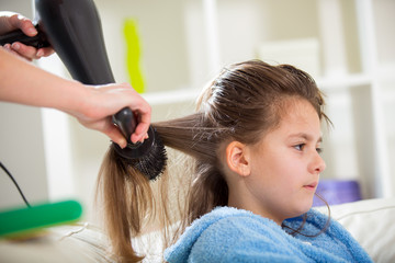 Mother dries hair teenage girl