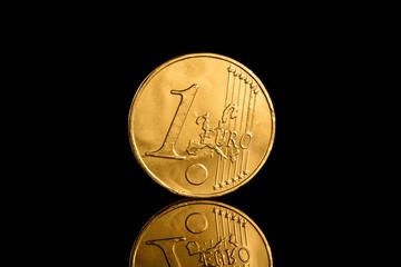 Goldene Euro-Münze spiegelnd auf schwarzem Untergrund. Die Mün