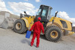 man in red uniform with petrol can at bulldozer back view
