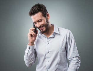 Smiling young businessman with smartphone