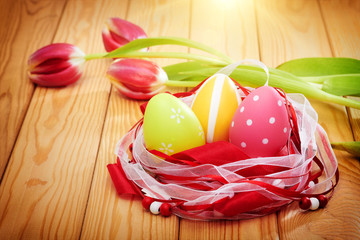 colorful easter eggs on wooden background with tulips