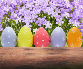 colorful easter eggs on nature background with spring flowers