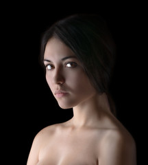 Portrait of a beautiful young brunette. Beauty on a black.