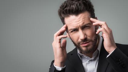 Businessman with headache head in hands