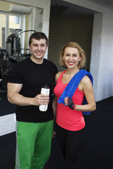 Fitness smiling couple in gym with water and towel