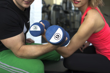 Couple are holding a dumbbells