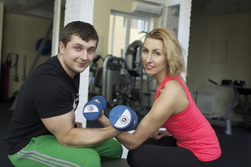 Fitness couple are holding a dumbbells