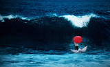 Man with red umbrella in a paperboat in the rough sea - 76430192