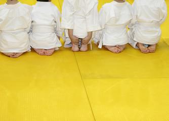 Children in kimono for martial arts sitting on tatami