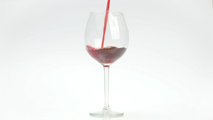 Red wine puoured in glass on white infinite background