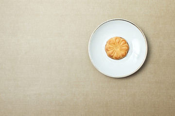 One cookie on a plate on beige background