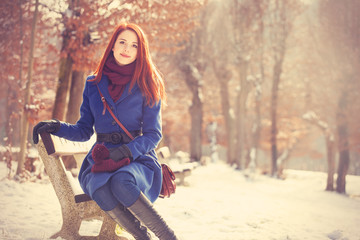 Redhead girl sitting on a bench in the winter park.