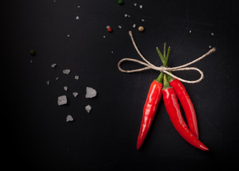 Three hot red chili pepper related by twine with sea salt and co
