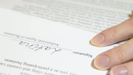 hand puts the signature on the document
