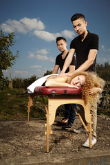 Two masseurs giving massage to woman outdoor