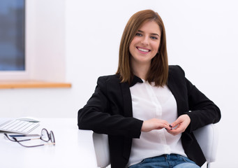 Portrait of a beautiful smiling woman sitting in the office