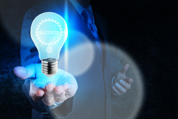 businessman hand showing light bulb with gear of success  as con