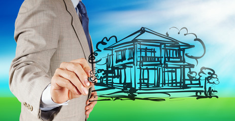 businessman hand drawing house