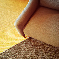 Textile armchair and knitted carpet in warm colors
