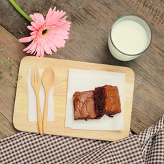 Tasty brownies with glass of milk and flower, retro filter effec