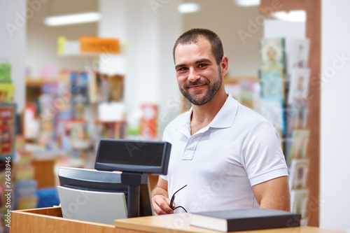 Salesman at the checkout in a bookstore - 76438946
