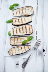 Grilled aubergine with green basil over white wooden surface