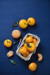 Wicker basket with ripe tangerines, dark blue wooden background
