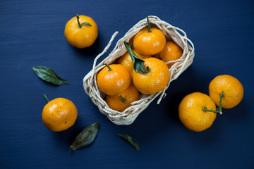 Ripe mandarins with leaves in a wicker tray, high angle view